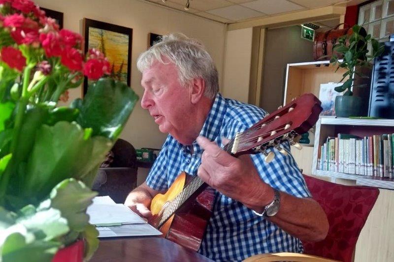 Kees speelt gitaar in de huiskamer
